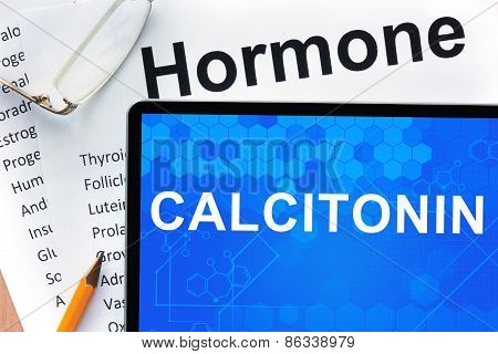 Papers with hormones list and tablet  with words Calcitonin.