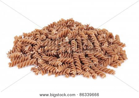 a pile of uncooked spelt fusilli on a white background