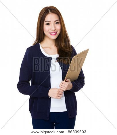 Attractive young woman writes with a clipboard