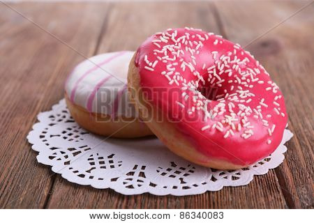 Delicious donuts with icing on lace doily on wooden background
