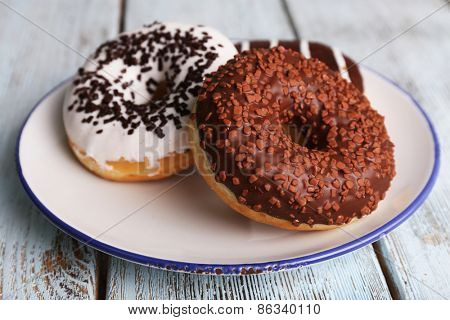 Delicious donuts with icing on plate on wooden background