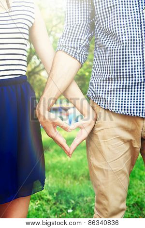 Loving couple holding hands in shape of heart, close-up