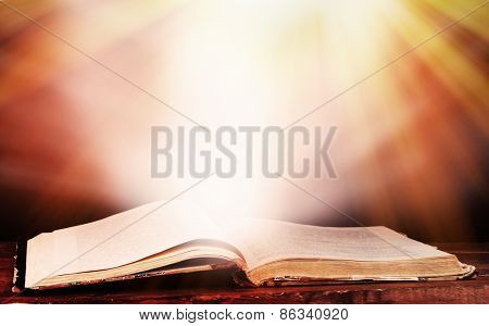 Opened book on table on brown background