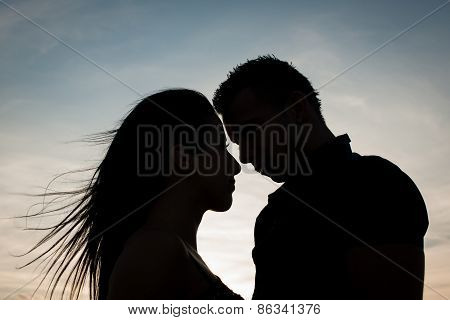 Silhouette of teenage couple in love on a late summer afternoon in park