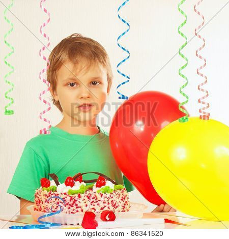 Young kid with festive cake and balloons