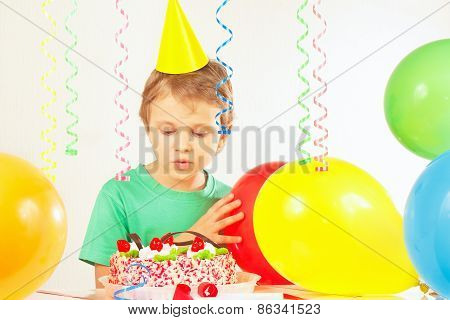Little blonde boy in festive cap looking at birthday cake