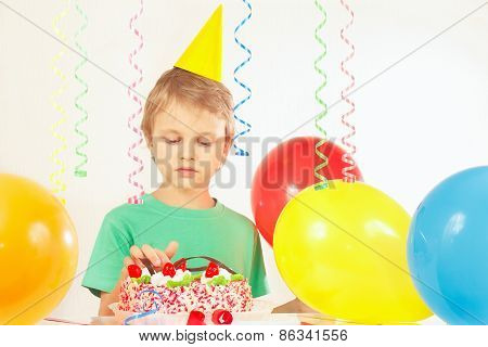 Little kid in festive hat looking at birthday cake