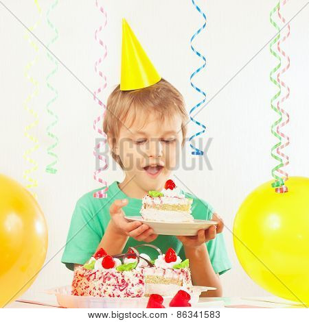 Young blonde boy in festive hat with piece of birthday cake