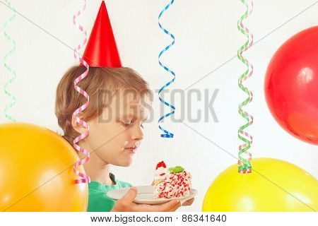 Young child in festive hat eating birthday cake