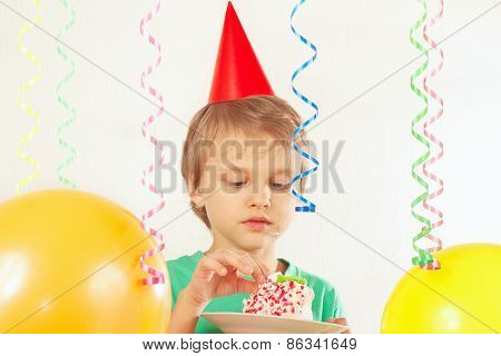 Little boy in festive hat eating piece of birthday cake