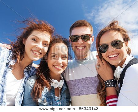 summer holidays and teenage concept - group of teenagers outdoors