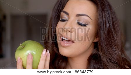 Gorgeous woman eating a healthy green apple looking at it with anticipation and her mouth open  close up of her hand with the fruit and face