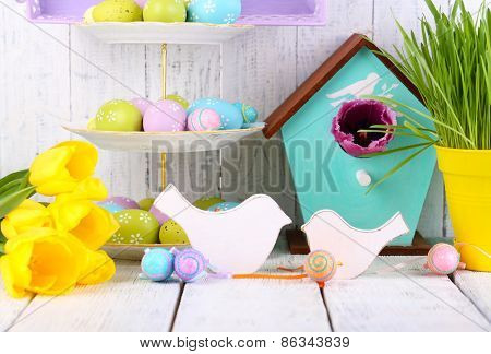 Easter decoration, eggs and tulips on table on wooden background