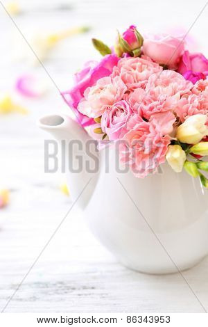 Beautiful spring flowers in teapot on wooden table, closeup