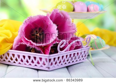 Tulips and Easter eggs on table on natural background