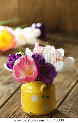 Beautiful spring flowers in yellow pot on wooden background