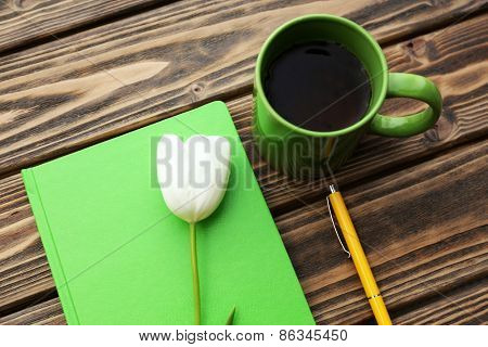 Notebook with cup of tea and white tulip on wooden background