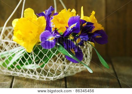 Beautiful spring flowers in wicker metal basket on wooden background
