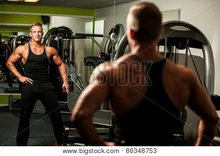 Handsome Man Looking In Mirror After Body Building Workout In Fitness