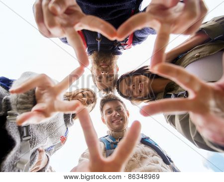 travel, tourism, hike, gesture and people concept - group of smiling friends with backpacks standing in circle and showing victory sign outdoors