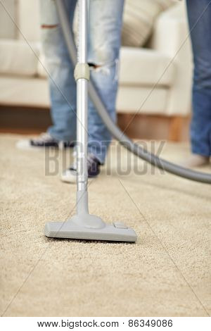 people, housework and housekeeping concept - close up of human legs and vacuum cleaner on carpet at home