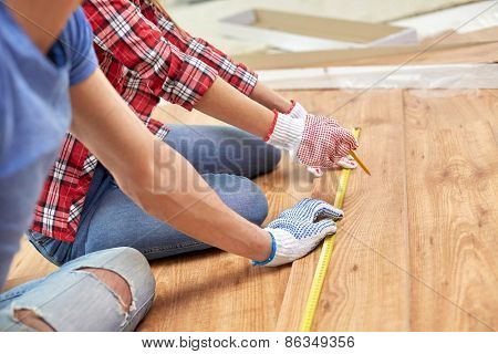 repair, building, flooring and people concept - close up of couple hands with ruler measuring parquet board at home