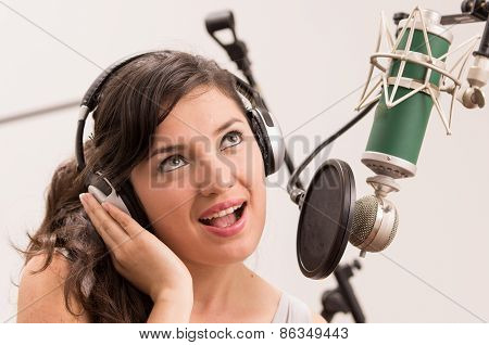 beautiful young girl singing in music studio
