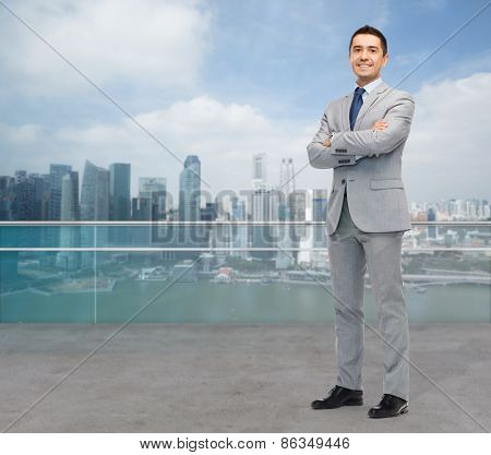 business and people concept - happy smiling businessman in suit over city background
