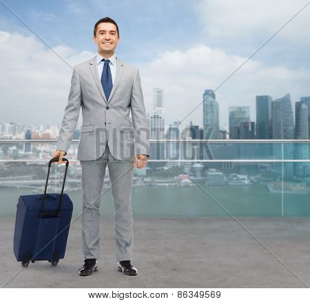 business trip, traveling, luggage and people concept - happy businessman in suit with travel bag over city background