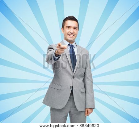 business, people and office concept - happy smiling businessman in suit pointing at you over blue burst rays background