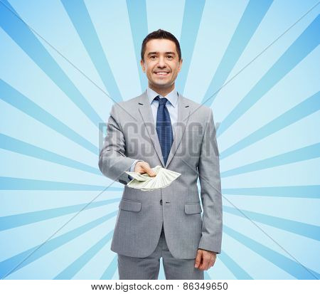 business, people and finances concept - smiling businessman with american dollar money over blue burst rays background