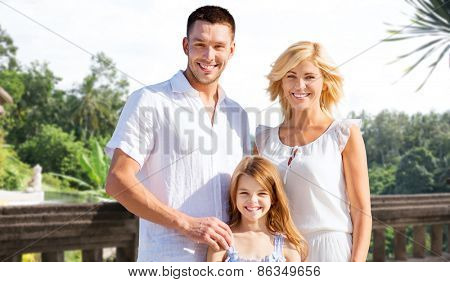 summer holidays, travel, tourism and people concept - happy family on vacation over villa balcony background