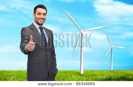 business, innovation, energy saving and people concept - handsome businessman showing thumbs up over windmills and blue sky background