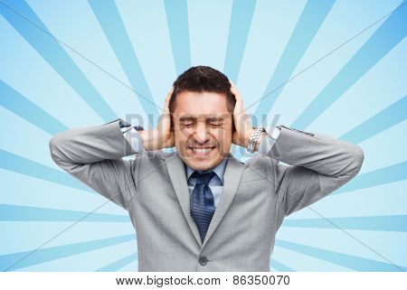 business, people, crisis and emotional pressure concept - businessman in suit covering his ears by hands over blue burst rays background