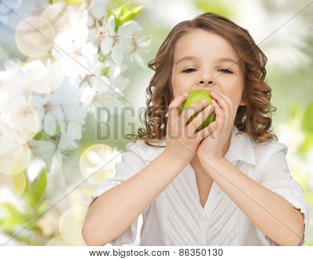 people, children, healthy eating, ecology and food concept- happy girl eating green apple over summer or spring garden background