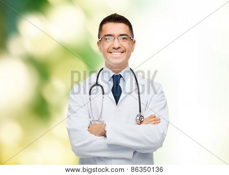 healthcare, profession, people and medicine concept - smiling male doctor in white coat over green background