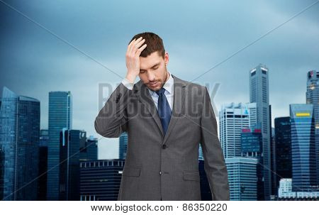 business, fail and crisis concept - young businessman having headache over city background