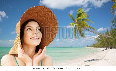 summer holidays, people, tourism, travel and vacation concept - happy young woman in straw hat over tropical beach background