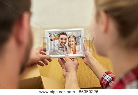 people, family, memories and moving concept - close up of happy couple looking at photo and unpacking things at new home