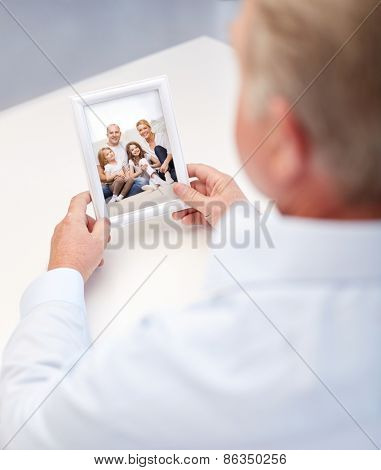 oldness, memories, nostalgia and people concept - close up of old man holding and looking at happy family photo