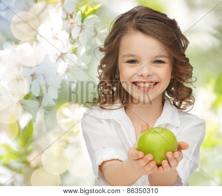 people, children, healthy eating, ecology and food concept- happy girl holding green apple over summer or spring garden background