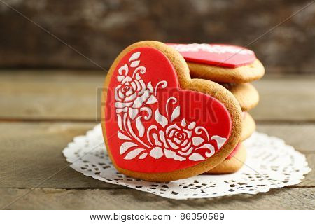Heart shaped cookies for valentines day on napkin, on color wooden background