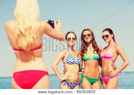 summer vacation, gesture, travel and people concept - group of smiling young women photographing by camera and waving hands on beach