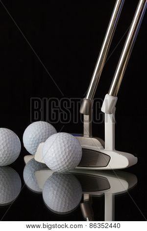 Two Different Golf Putters And Three Golf Balls