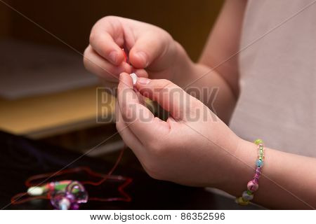 Child's Hands Strung Beads On Thread