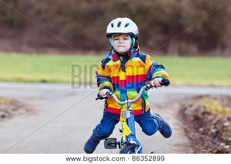 Funny cute preschool kid boy in safety helmet and colorful raincoat riding his first bike