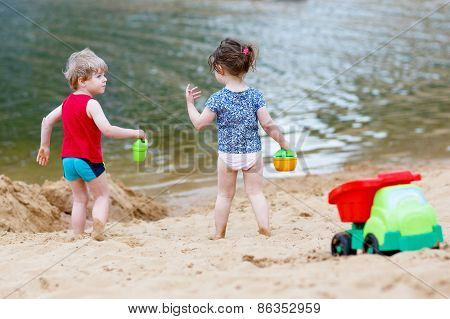 Little Toddler Boy And Girl Playing Together With Sand Toys Near Lake