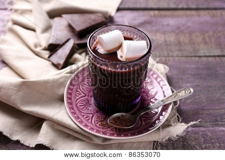 Hot chocolate with marshmallows in glass, on color wooden background