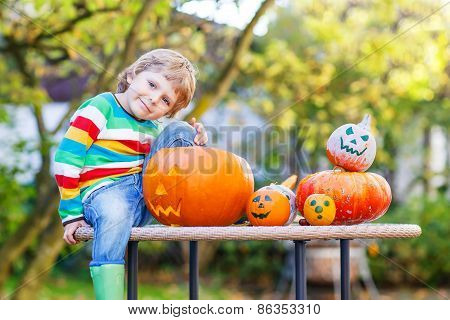 Little Kid Boy Making Jack-o-lantern For Halloween In Autumn Garden