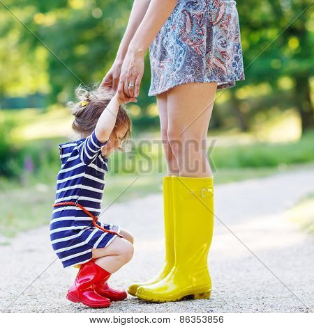 Mother And Little Adorable Child Girl In Rubber Boots Having Fun Together